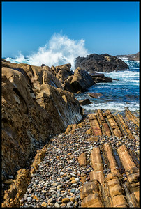 Interesting geological formations amidst the crashing waves.